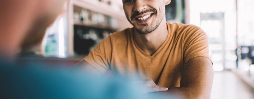 Happy young male in casual clothes enjoying pleasant conversation with friend while sitting at table during meeting in modern cafeteria